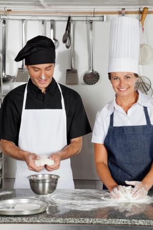 Chefs Kneading Dough In Kitchen Stock Photo - 18029378