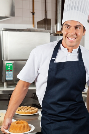 Male Chef Holding Baked Cake In Kitchen Stock Photo - 18029444