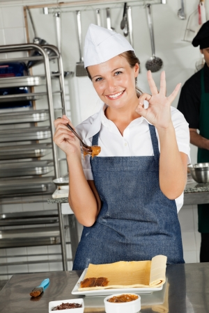 Female Chef Showing Okay Sign In Kitchen Stock Photo - 18029425