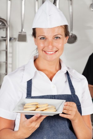 Happy Female Chef Presenting Cookies photo