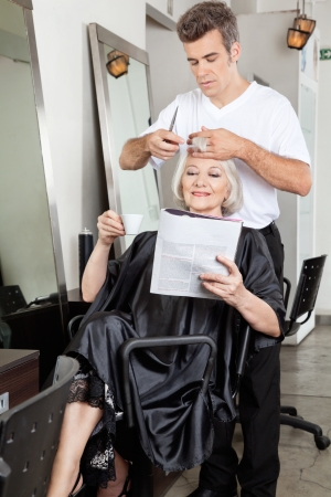 Woman Reading Magazine While Having Haircut photo