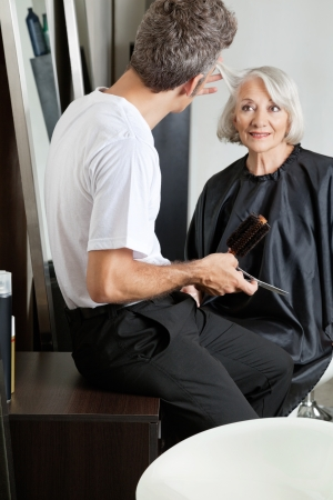 Hairdresser Examining Customer s Hair At Parlor Stock Photo - 18068577