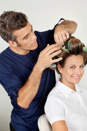 Customer With Hairstylist Curling Hair At Parlor photo