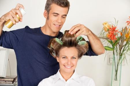 hairdresser's parlor: Client With Hairdresser Setting Curls With Hairspray