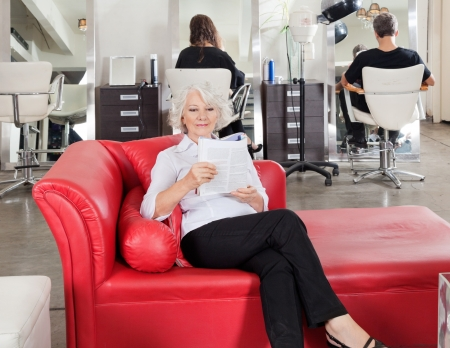 Woman Reading Magazine With Clients Waiting For Hairdresser photo