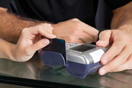 Hand Swiping Credit Card Through Terminal At Salon photo