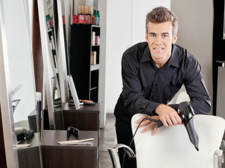 Male Hairstylist With Hairdryer Leaning On Chair Stock Photo - 18068549