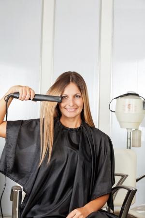 Woman Straightening Her Hair While Sitting On Chair photo
