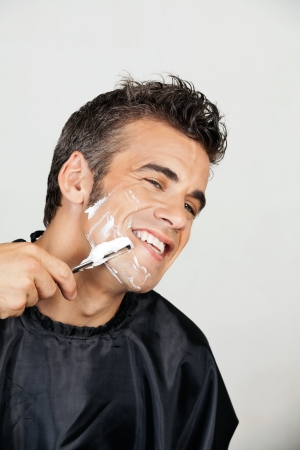 straight razor: Happy Man Shaving His Face Stock Photo