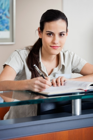 Female Receptionist Writing In Book photo