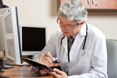 Doctor Reading While Sitting At Desk Stock Photo