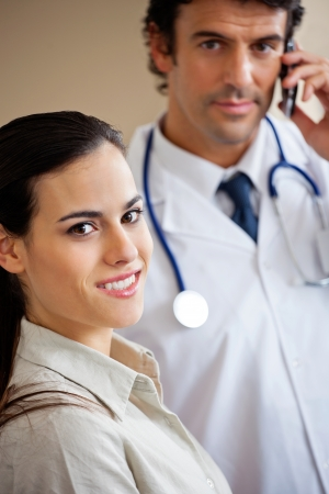 Woman Smiling While Doctor Standing In Background photo