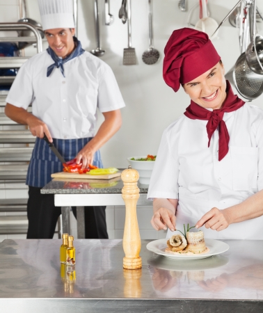 Female Chef Garnishing Dish In Kitchen photo