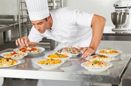 garnishing: Chef Garnishing Dishes At Counter