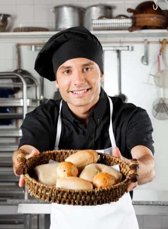 Male Chef Offering Breads In Kitchen photo