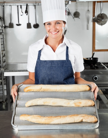 baking tray: Female Chef Presenting Loafs In Kitchen