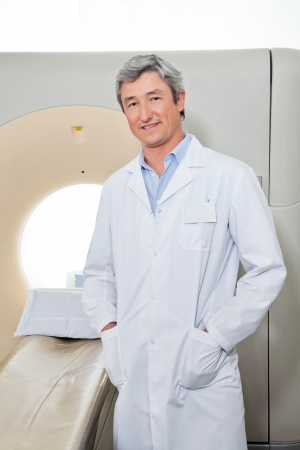 Doctor Standing Next To CT Scanner photo