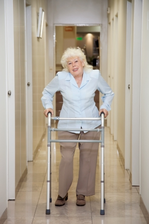 Elderly Woman With Walker In Hospital Corridor photo