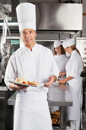 Chef Presenting Dish In Commercial Kitchen photo