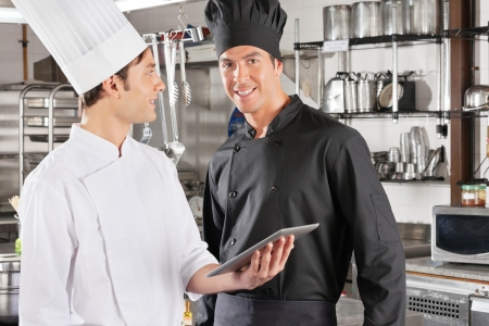 waistup: Chef With Colleague Holding Digital Tablet Stock Photo