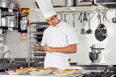 cocinas industriales: Cocinero de sexo masculino que usa la tableta digital en la cocina