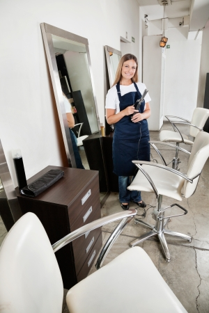 hairdresser parlor: Hairdresser Holding Hair Straightener In salon