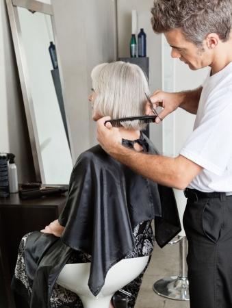 salon beaut�: Femme obtenant Hair Cut En Beauty Parlor Banque d'images