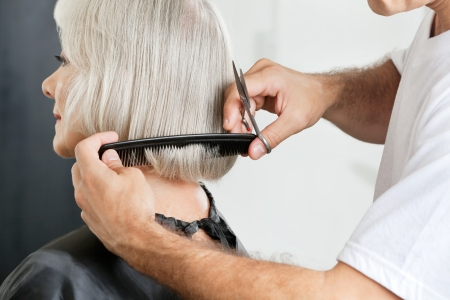 hair cut: Hairstylist Measuring Hair Length Before Haircut Stock Photo