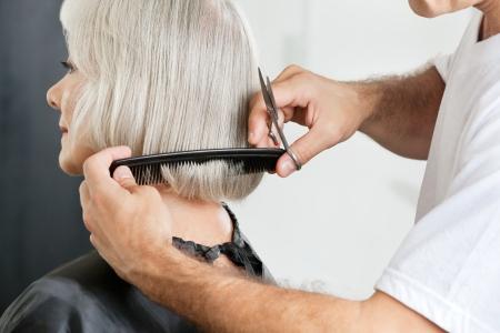 cut hair: Hairstylist Measuring Hair Length Before Haircut Stock Photo