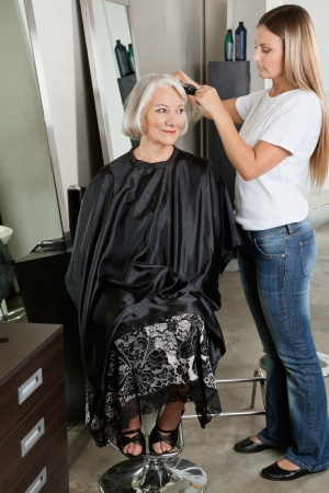 Hairdresser Straightening Woman s Hair At Parlor photo