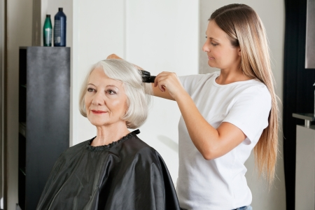 Client Having Hair Straightened By Hairstylist Stock Photo