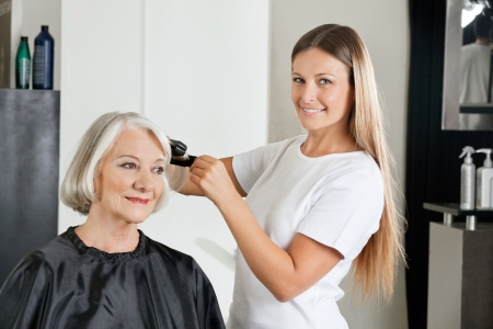 Hairdresser Ironing Customer s Hair Stock Photo