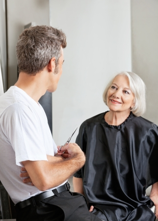 woman short hair: Woman Having Conversation With Hairdresser Stock Photo