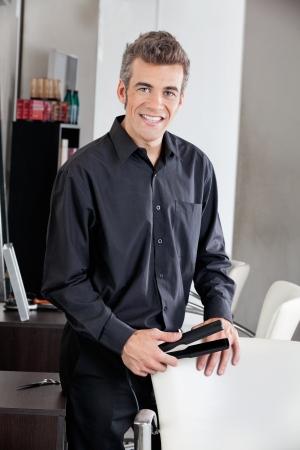 straightener: Happy Hairdresser Holding Straightener