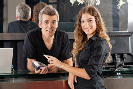 wallet: Hairdresser With Woman Paying Through Cellphone At Counter Stock Photo