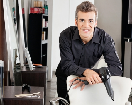 Hairstylist With Blower Leaning On Chair Stock Photo - 18136822