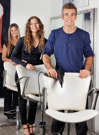 Confident Hairdressers With Hairdryer And Scissors In Salon photo