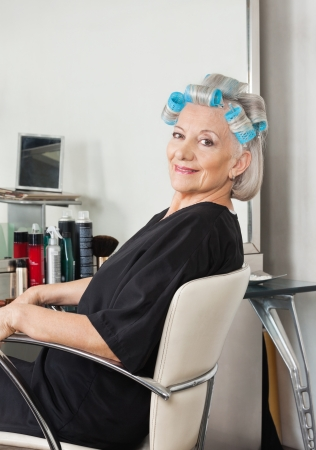 Woman With Hair Curlers Sitting On Chair At Salon photo