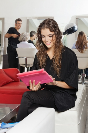 Client Using Tablet With Hairdresser And Women In Salon photo