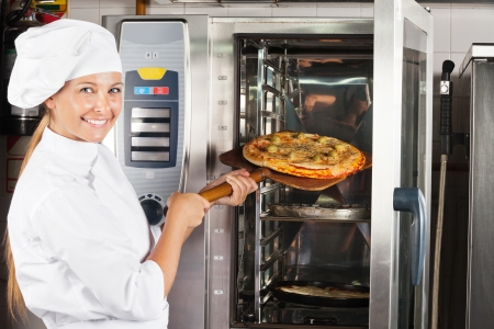 Beautiful Chef Placing Pizza In Oven photo