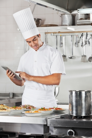 Chef Using Tablet With Pasta Dishes At Counter photo