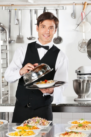 serving: Waiter Lifting The Cover Of Cloche