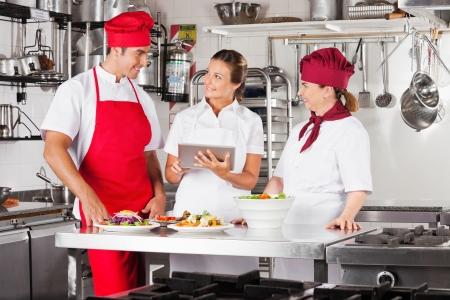 cocinas industriales: Chefs Uso de Tablet PC en el mostrador de la cocina Foto de archivo