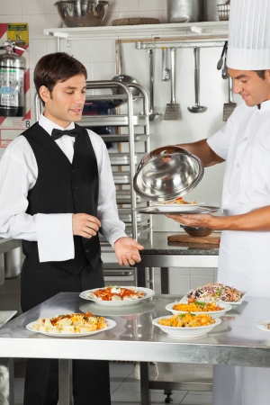 Chef Giving Customer s Food To Waiter photo