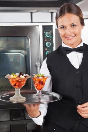 Happy Waitress Holding Dessert Tray photo