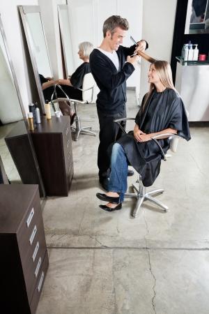 Hairstylist Cutting Customer s Hair In Salon photo