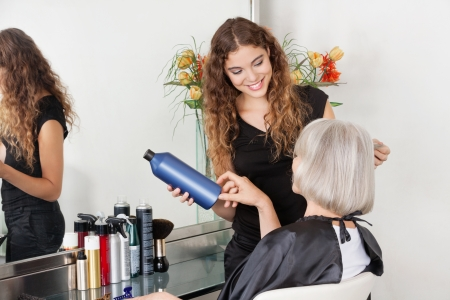 Hairstylist Advising Hair Color To Senior Client photo