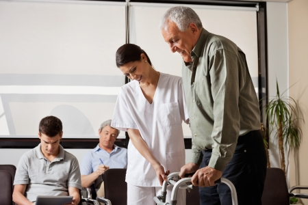 walker: Man Being Assisted By Nurse To Walk Zimmer Frame