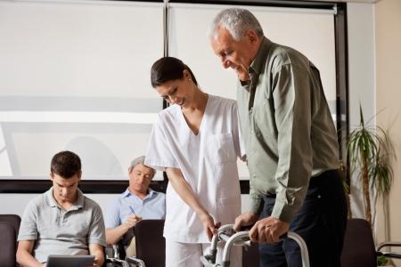 gehhilfe: Mann, der von Nurse Assisted Um Zimmer Rahmen Gehen Lizenzfreie Bilder