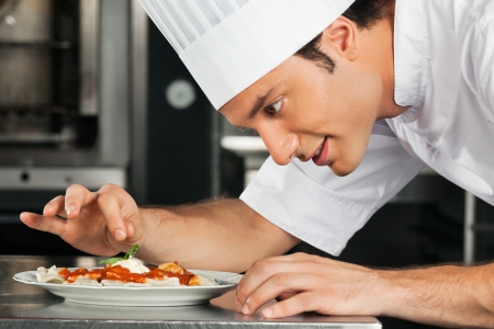 commercial kitchen: Male Chef Garnishing Dish Stock Photo